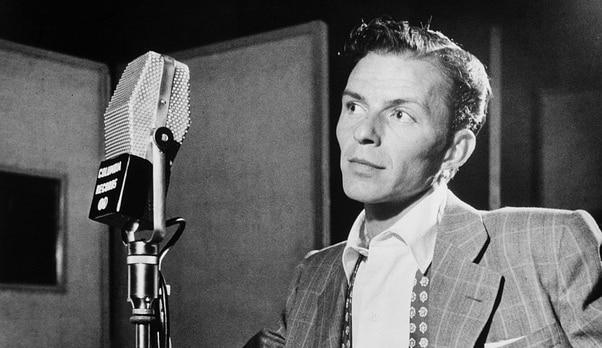 Frank Sinatra devant un micro dans un studio d'enregistrement.